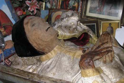 """Η χαριτόβρυτη ιερή μούμια του ορθόδοξου Ρουμάνου ιερέα Ilie Lăcătușul, φίλου της ορθόδοξης, φασιστικής, αντισημιτικής «Λεγεώνας του «Αρχάγγελου Μιχαήλ» (ή «Σιδηράς Φρουράς») και «ιεραπόστολου» στη Βεσσαραβία και στην Υπερδνειστερία στη διάρκεια της ναζιστικής κατοχής της το 1942-1943, οπότε εκατοντάδες χιλιάδες Εβραίοι και Ρομά εξοντώθηκαν κάτω από τη Ρουμανογερμανική φασιστική εξουσία (Irina Stahl-Institute of Sociology Romanian Academy, """"The Romanian Saints: Between Popular Devotion and Politics"""", βραβευμένο το 2014 από την American Folklore Society."""